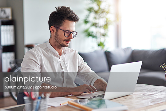 Businessman working on laptop at home office - p300m2012202 von gpointstudio
