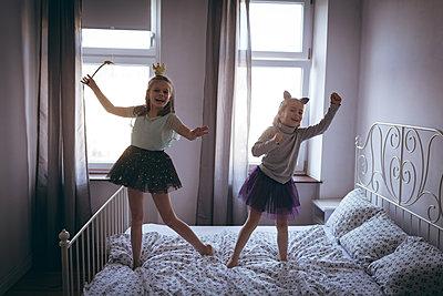 Girls in costume dancing on bed in bedroom - p1315m1565520 by Wavebreak
