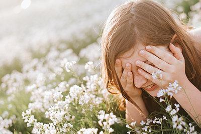 Teenager spielt Verstecken in einer Blumenwiese - p1507m2172025 von Emma Grann