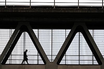 Silhouette eines Fußgängers auf einer Brücke - p1638m2291851 von Macingosh
