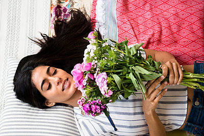Indian woman laying on bed holding bouquet of flowers - p555m1305072 by JGI/Jamie Grill