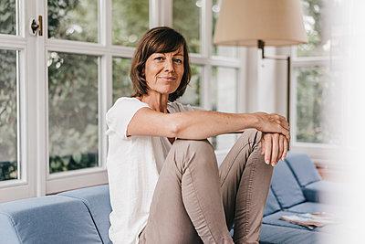 Reife Frau entspannt auf dem Sofa - p586m1178525 von Kniel Synnatzschke