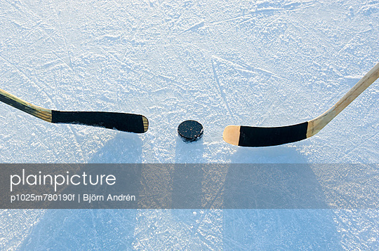 Close-up of hockey sticks and puck on sand