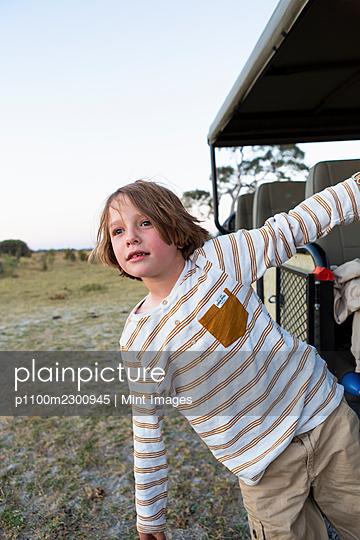 Young boy holding onto safari vehicle, Okavango Delta, Botswana. - p1100m2300945 by Mint Images