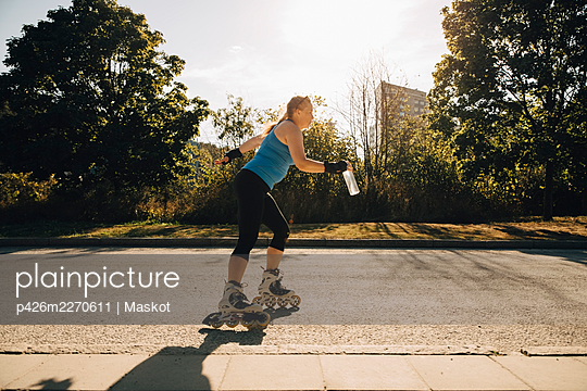 Female athlete roller skating on street during sunny day - p426m2270611 by Maskot