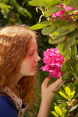 Mädchen riecht den Duft der Blüte - p045m1461158 von Jasmin Sander