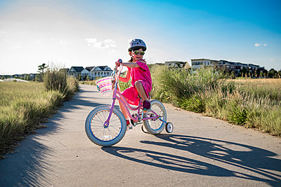 Girl riding bicycle with training wheels on road against sky during sunny day - p1166m1509632 by Cavan Images