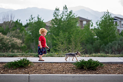 Side view of cute baby boy walking with puppy on footpath in park - p1166m2067849 by Cavan Images