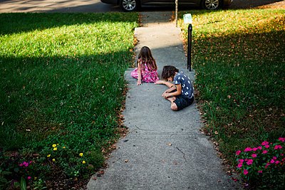 a brother and sister sit barefoot in their yard in summer - p1166m2078473 by Cavan Images