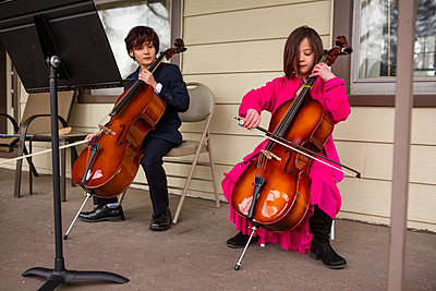 A boy holding cello looks on while his sister plays her instrument - p1166m2250670 by Cavan Images