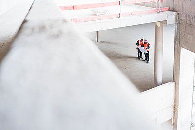 Two men with plan wearing safety vests talking in building under construction - p300m1460460 by Daniel Ingold