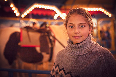 Portrait of girl wearing sweater standing at illuminated carnival in city during night. Munich, Germany - p300m2197724 by Studio 27
