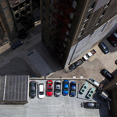 High angle view of city buildings and parked cars - p301m960833f by Peter Baker