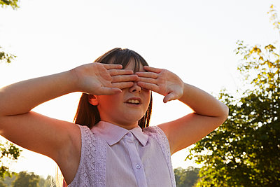 Girl covering eyes for hide and seek in park - p429m1407860 by Emma Kim