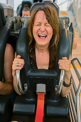 Caucasian woman shouting on roller coaster - p555m1459420 by Eric Raptosh Photography