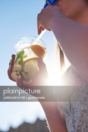 Woman drinking lemonade from plastic cup, close-up - p300m2012196 von gpointstudio