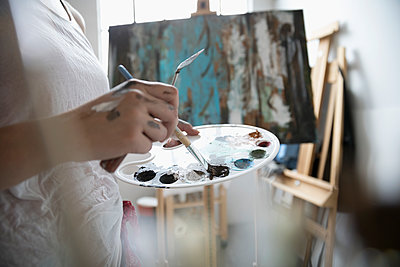 Close up female painter dipping paintbrush into palette, painting at canvas - p1192m1490241 by Hero Images