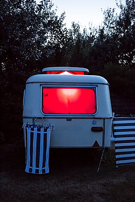Caravan at dusk, illuminated by a red light with striped towels hanging to dry - p1682m2260611 by Régine Heintz