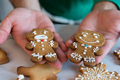 Man's hands holding two different Gingerbread Men, close-up - p300m2005383 von skabarcat