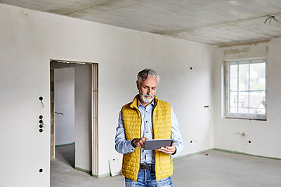 Mature man using tablet on a construction site - p300m2199319 by MiJo