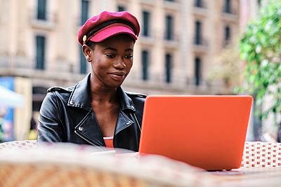 Smiling woman wearing cap working on laptop while sitting at sidewalk cafe - p300m2250169 by Alvaro Gonzalez