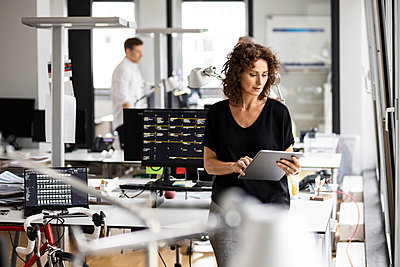 Businesswoman using digital tablet with colleague standing in background at open plan office - p300m2257078 by Peter Scholl