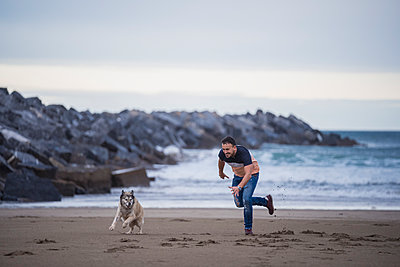 Playful man running with dog at beach against sky - p300m2257279 by SERGIO NIEVAS