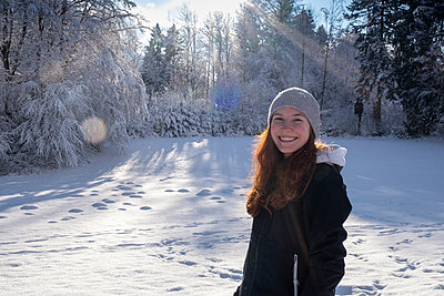 Smiling beautiful woman standing on snow during sunny day - p300m2282309 by Lisa und Wilfried Bahnmüller