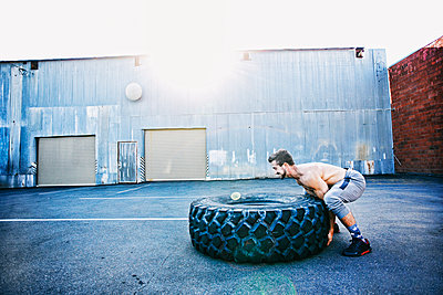 Caucasian man working out with heavy tire outdoors - p555m1304125 by Peathegee Inc