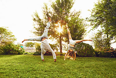 Male and female adult friends doing cartwheels in park - p924m1230122 by Matt Monath