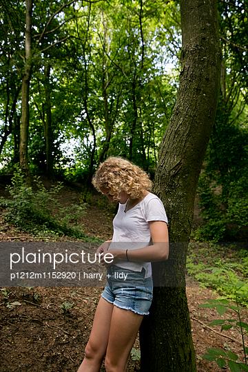 Mädchen lehnt an einem Baum im Wald - p1212m1152920 von harry + lidy