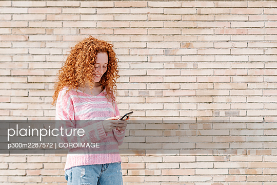 Young woman with curly hair using mobile phone while standing n front of brick wall - p300m2287572 by COROIMAGE