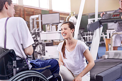 Smiling physical therapist talking to man in wheelchair - p1023m1121413f by Trevor Adeline