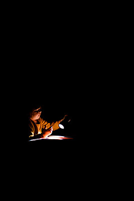 Preschooler girl playing with a flash light on her bed in a bedroom - p1166m2268980 by Cavan Images