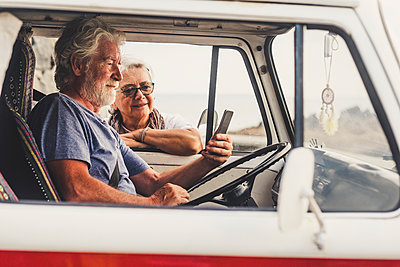 Senior couple traveling in a vintage van, using smartphone - p300m2114895 von Simona Pilolla