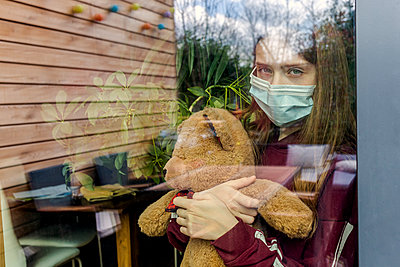 Portrait of girl with surgical mask and teddy bear behind window pane - p300m2180583 by Sandra Roesch