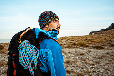 Thoughtful male hiker looking away while standing on mountain against sky - p300m2241081 by Rafa Cortés
