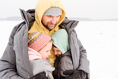 Father covering children in his coat while standing on land during winter - p300m2251245 by Ekaterina Yakunina