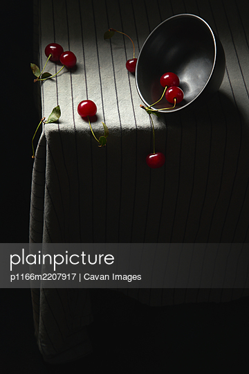 Juicy red cherries and an inverted bowl on a striped tablecloth. - p1166m2207917 by Cavan Images