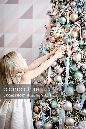 Little girl stouching decoration of Christmas tree - p300m2139847 by Ekaterina Yakunina