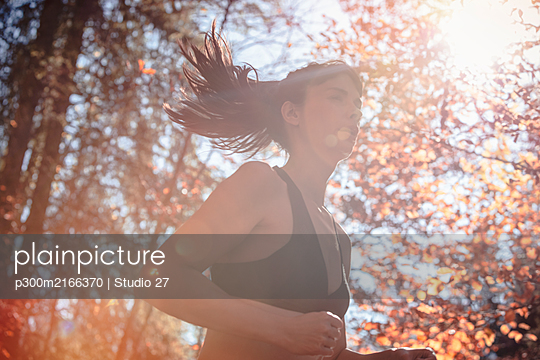 Woman jogging in autumn forest - p300m2166370 by Studio 27