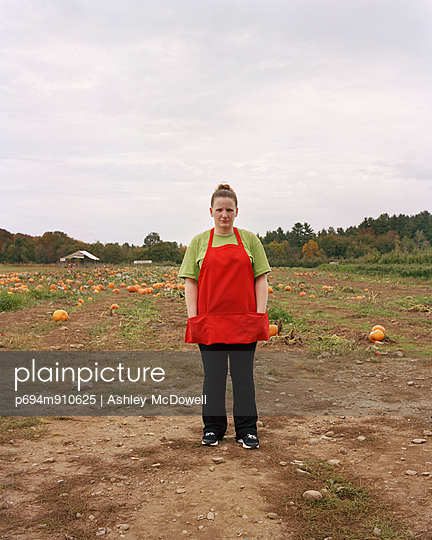 Woman Wearing Red Apron Standing in Pumpkin Patch