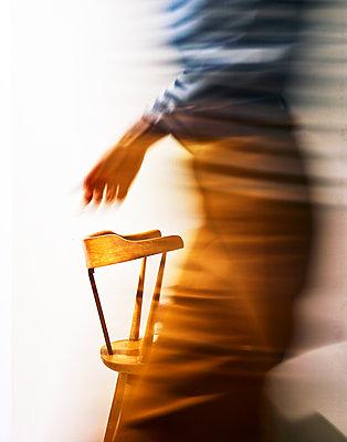 Weibliche Person geht schnell an einem Stuhl vorbei, Bewegungsunschärfe - p1397m2184318 von David Prince