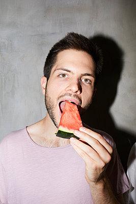 Young man bites into a piece of melon - p276m2115593 by plainpicture