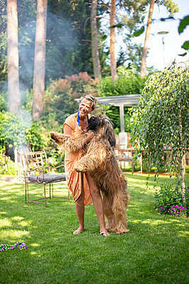 Woman playing with dog in garden - p300m2155529 by Bernd Friedel