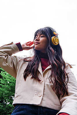 Woman listening music through headphones - p300m2293273 by Angel Santana Garcia