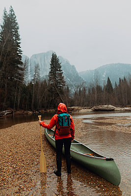 Young female canoeist preparing canoe in river, rear view, Yosemite Village, California, USA - p924m2097947 by Peter Amend