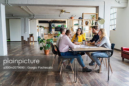 Business team having a meeting in loft office - p300m2079690 by Giorgio Fochesato