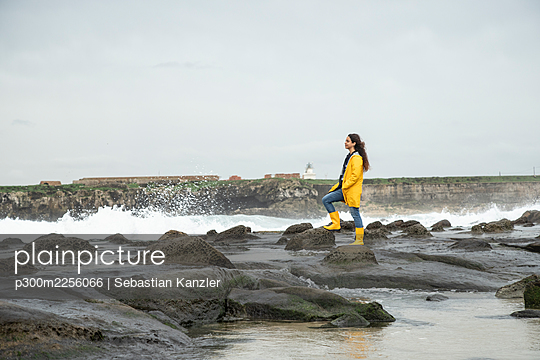 Woman looking at view while standing on coastline rock - p300m2256066 by Sebastian Kanzler