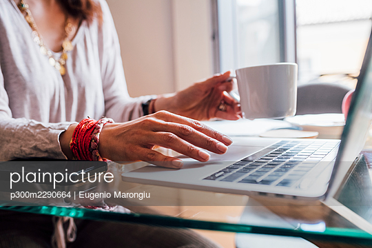 Woman holding coffee cup while using laptop at home - p300m2290664 by Eugenio Marongiu